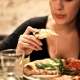 woman-holds-sliced-pizza-seats-by-table-with-glass-723031-Cropped-1-1068x601